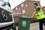 Man pushing green garden waste wheelie bin to lorry