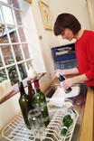 Woman washing glass bottles at kitchen sink for recycling
