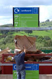 Man placing flattened cardboard boxes into cardboard recycling point