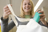 Woman packing shopping at checkout in re-usable fabric shopping bag