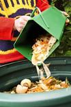 Man emptying food waste caddy into compost bin - tea bags, veg peelings, egg shells