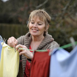 Woman hanging washing on line in garden