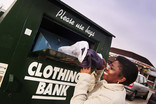 Woman putting carrier bag of clothes into a clothing bank