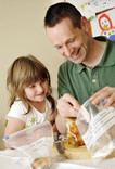 Father and daughter putting leftover chicken in labelled freezer bags