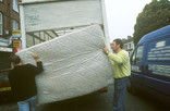 Two men lifting a mattress into a van for re-use