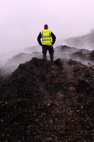 Man standing on mounds of compost