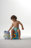 Baby with toy and stack of re-usable nappies