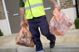 Man collecting two orange recycling sacks outside houses