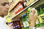 Man choosing can of Lilt in supermarket