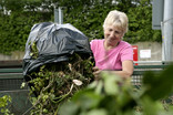 Woman emptying bin bag of garden waste at recycling centre