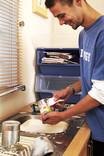 Man washing soup tin for recycling