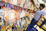 Woman choosing magazine in supermarket