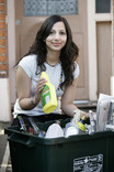 Woman recycling plastic bottle at kerbside recycling bin