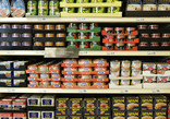 Shelves of tinned vegetables and meat in supermarket