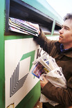 Man putting bag of magazines and newspapers in paper bring bank
