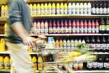 Man pushing trolley past shelves of bottles of squash in supermarket