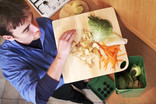 Man putting vegetable peelings in food waste caddy