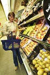 Woman choosing apples in supermarket - man in background