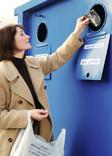 Woman recycling cans at bring bank