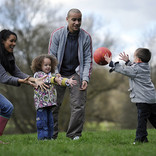 Young family playing with ball in park