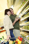 Man and woman choosing ready meals in supermarket with shopping trolley