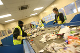 Workers sorting recycling at a Materials Recycling Facility