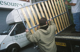 Two men lifting a bed frame into a van for re-use