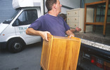 Man lifting furniture into van for re-use