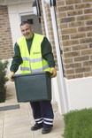 Man lifting green recycling container outside house