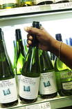 Choosing bottle of wine in supermarket - green bottle