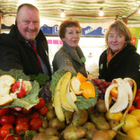 Man and two women holding fruit and vegetable peelings at fresh produce market stall