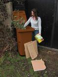 Woman putting garden waste and cardboard into brown wheelie bin