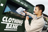 Man putting carrier bag of clothes into a clothing bank