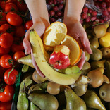 Hands holding fruit peelings with fresh fruit stall as background