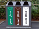 Green, brown and clear glass recycling bin on street