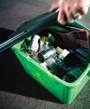 Putting lid on full recycling bin with cans, glass and paper