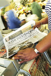 Woman choosing a newspaper from supermarket stand