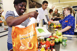 Woman packing food shopping in plastic bag for life at supermarket checkout