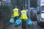 Crew collecting green recycling bags on street