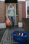 Man putting orange recycling bag and blue recycling container out for kerbside collection