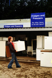 Woman lifting small fridge at fridges and freezers recycling point