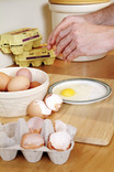 Cracking eggs for cooking in kitchen