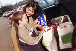 Woman and boy putting re-usable bags with shopping into car boot
