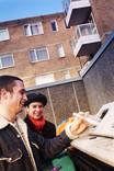 Man and woman recycling glass in a communal recycling bin with flats in background