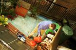 Man composting in courtyard garden