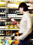 Woman choosing bottle of wine in supermarket