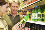 Man and woman choosing soft drinks in supermarket