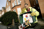 Man emptying green recycling container of paper and card into wheelie bin