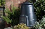 Compost bin in garden with brick wall