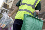 Man collecting clear recycling sacks and green sack outside house